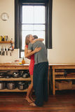 Cheerful young couple embracing each other in kitchen Royalty Free Stock Photography