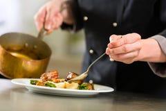 Chef-kok in hotel of restaurantkeuken het koken Stock Afbeelding