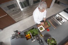 Chef Slicing Cucumber On Board At Commercial Kitchen Counter Stock Image