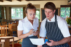 Chef And Waitress Discussing Menu In Restaurant Royalty Free Stock Photos