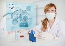 Chemist working in protective suit with futuristic interface showing a brain Stock Photography