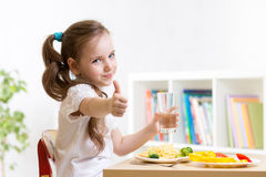 Child eats healthy food showing thumb up Stock Images