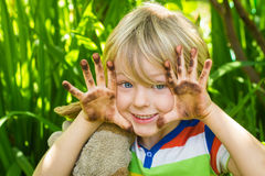 Child in garden with dirty hands Royalty Free Stock Image
