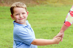 Child holding hands with parent while going for walk Stock Image