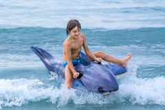 Child playing with inflatable shark in waves Royalty Free Stock Image