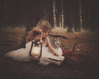 Child Reading Book with Owl in Dark Woods Royalty Free Stock Photos