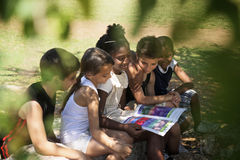 Children and education, kids and girls reading book in park Royalty Free Stock Images