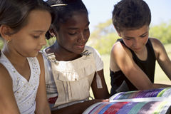 Children and education, kids and girls reading book in park Royalty Free Stock Photo