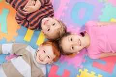 Children lying on backs on fun kids alphabet mat Royalty Free Stock Photos