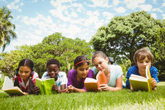 Children lying on grass and reading books Stock Photos