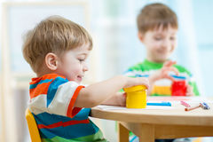 Children play and paint at home or kindergarten or playschool Royalty Free Stock Images