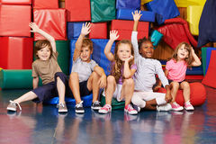 Children raising their hands in gym of school Royalty Free Stock Photos