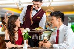 Chinese waiter serving dinner in elegant restaurant or Hotel Royalty Free Stock Photography