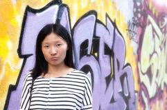 Chinese woman against urban art wall Royalty Free Stock Images