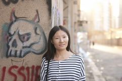 Chinese woman against urban art wall Royalty Free Stock Image