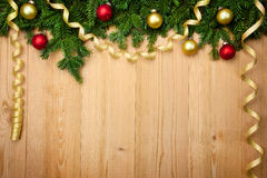 Christmas background with firtree, baubles and ribbons on wood Stock Image