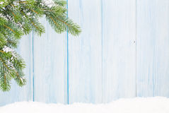 Christmas fir tree in snow in front of wooden wall Royalty Free Stock Images
