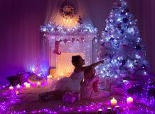 Christmas Night Room Kids under Lights Tree, Children Girls Home Stock Photo