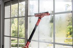 Cleaning window with steam Royalty Free Stock Photography