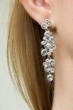 Close up of woman wearing shiny diamond earrings Stock Photo