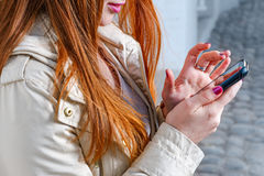 Closeup av redhairflickan som smsar på mobiltelefonen Arkivfoton
