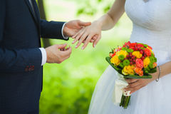 Closeup of hands of bridal unrecognizable couple with wedding rings. bride holds wedding bouquet of flowers. Royalty Free Stock Photos