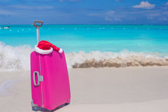 Closeup of pink luggage and Santa Claus hat on tropical beach Stock Images