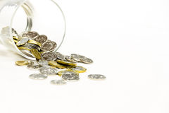 Coins spilling from a money jar. Royalty Free Stock Images
