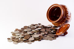 Coins spilling from the pot Royalty Free Stock Images