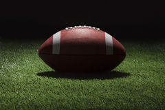 College football on grass field at night with spot lighting Stock Photo