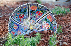 Colorful plate in the flowerbed Royalty Free Stock Photo