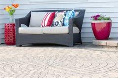 Comfortable modern settee on an outdoor patio Stock Photos