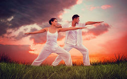 Composite image of peaceful couple in white doing yoga together in warrior position Royalty Free Stock Photos