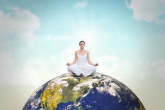 Composite image of peaceful woman in white sitting in lotus pose Stock Photography