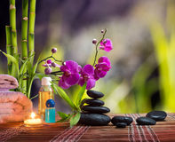 Composition spa massage - bamboo - orchid, towels, candles and black stones Stock Image