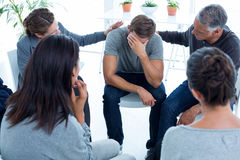 Concerned patients comforting another in rehab group Stock Photo
