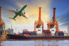 Container ship loading on port and cargo plane flying above for water and air transportation industry Stock Photos
