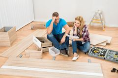 Contemplated couple with disassembled furniture Stock Images