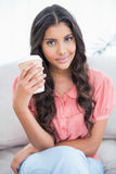 Content cute brunette sitting on couch holding disposable cup Stock Image