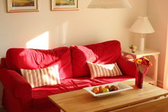 Cosy red couch in summerhouse in the afternoon Stock Image