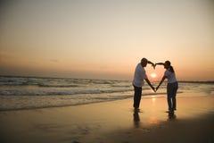 Couple on beach at sunset. Stock Image