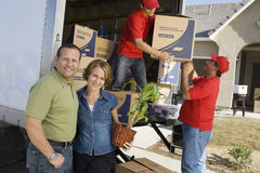 Couple With Delivery Men Unloading Moving Boxes From Truck Royalty Free Stock Photos