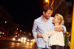 Couple embracing on city street at night, portrait Royalty Free Stock Image
