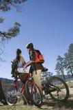 Couple With Mountain Bikes In Recreation Area Stock Photos