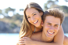 Couple with perfect smile posing on the beach Stock Images