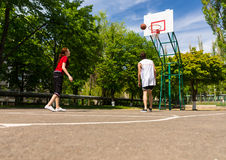 Couple Playing Basketball on Outdoor Court Stock Image