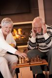 Couple playing chess in cosy living room Stock Photography