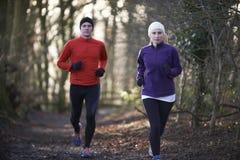 Couple On Winter Run Through Woodland Stock Photo