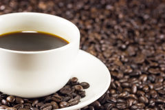 Cup of coffee and coffee beans background, warm toning Stock Images