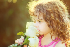 Curly baby with flowers in her hand. Toning photo. Instagram fil Stock Image